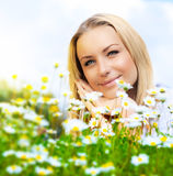 Beautiful woman enjoying daisy field and blue sky. Nice female lying down in the meadow of flowers, pretty girl relaxing outdoor, happy young lady and green Royalty Free Stock Photography