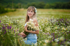 Beautiful woman enjoying daisy field, nice female lying down in meadow of flowers, pretty girl relaxing outdoor, having fun, holdi. Ng plant, happy young lady Stock Photo