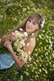 Beautiful woman enjoying daisy field, nice female lying down in meadow of flowers, pretty girl relaxing outdoor, having fun, holdi Stock Images