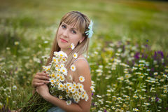 Beautiful woman enjoying daisy field, nice female lying down in meadow of flowers, pretty girl relaxing outdoor, having fun, holdi. Ng plant, happy young lady Royalty Free Stock Photo