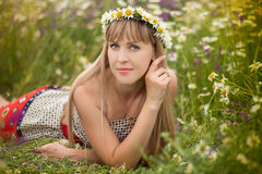 Beautiful woman enjoying daisy field, nice female lying down in meadow of flowers, pretty girl relaxing outdoor, having fun, holdi Royalty Free Stock Image