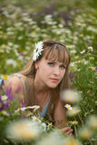Beautiful woman enjoying daisy field, nice female lying down in meadow of flowers, pretty girl relaxing outdoor, having fun, holdi. Ng plant, happy young lady Stock Image
