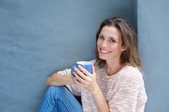 Beautiful woman enjoying a drink of a coffee stock photography