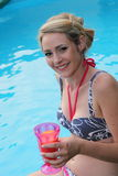 Beautiful woman enjoying a drink at the pool Royalty Free Stock Photo