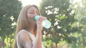 Beautiful woman enjoying drinking water after outdoor workout