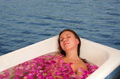 Beautiful woman enjoying floral bath Stock Photos