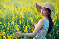 Beautiful woman enjoying with flowers on field. Holding plant, lady touching nature, aromatherapy concept stock images