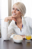 Beautiful woman enjoying a healthy breakfast. Beautiful stylish young woman with a friendly smile seated at a table enjoying a healthy breakfast Royalty Free Stock Photo