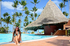 Beautiful woman enjoying her tropical vacantion near the pool Royalty Free Stock Image