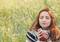 Beautiful woman enjoying hot drink in autumn cold day. Beautiful woman enjoying scent of hot drink in autumn cold day royalty free stock photography
