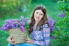 Beautiful woman enjoying lilac garden, young woman with flowers in green park. girl tearing the lilac in the garden royalty free stock photo