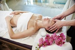 Beautiful Woman Enjoying Massage in SPA. High angle portrait of young women enjoying face and head massage lying on table in SPA center and relaxing Royalty Free Stock Photos