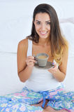 Beautiful woman enjoying morning coffee in bed Stock Photos