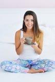 Beautiful woman enjoying morning coffee in bed Stock Photo