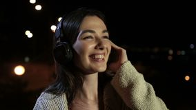Beautiful woman enjoying music in night city stock video footage