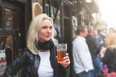 Beautiful woman enjoying a pint of beer in London Royalty Free Stock Photos