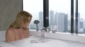 Beautiful Woman enjoying relaxing bath in luxury bathroom with a window. Lifestyle and beauty care concept. view from. The window to the skyscrapers royalty free stock photography