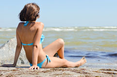 Beautiful woman enjoying sea view on sandy beach. Young beautiful woman enjoying looking at sea on sandy beach on summer outdoors background Royalty Free Stock Photography