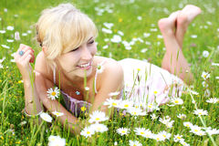 Beautiful woman enjoying the summer. Beautiful young blond woman enjoying the summer lying barefoot on her stomach in a field of white daisies smiling with Stock Image