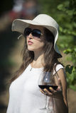 Beautiful woman enjoying in vineyard and holding glass of wine. Royalty Free Stock Images