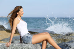 Beautiful woman enjoying the wind on the beach. With the sea in the background Stock Photos