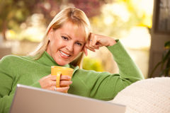 Beautiful Woman Enjoys Her Warm Drink and Laptop stock photo