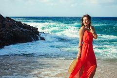 Beautiful woman enjoys the view of waves on the beach. Girl relaxing and enjoying vacation walking by sea royalty free stock photos