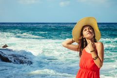 Beautiful woman enjoys the view of waves on the beach. Girl relaxing and enjoying vacation walking by sea stock image