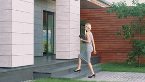 Beautiful woman entering business office with laptop. Female boss arriving work