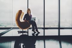 Charming businesswoman on armchair with laptop royalty free stock image
