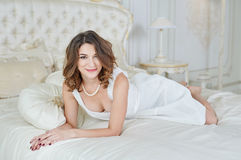 Beautiful woman in evening dress with decollete lying on bed Royalty Free Stock Photo