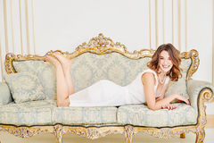 Beautiful woman in evening dress with decollete lying on bed Stock Photos