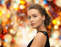 Beautiful woman in evening dress wearing earrings. People, holidays, christmas and glamour concept - beautiful woman in evening dress wearing earrings over red Royalty Free Stock Photos