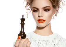 Beautiful woman with evening make-up holding a king chess piece Stock Photography