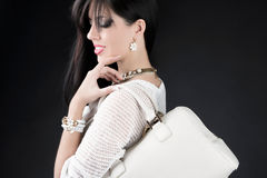 Beautiful woman with evening make-up. Jewelry, bag and Beauty. Royalty Free Stock Image