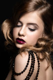 Beautiful woman with evening make-up, red lips and curls. Beauty face. Royalty Free Stock Photography
