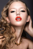 Beautiful woman with evening make-up, red lips and curls. Beauty face. Royalty Free Stock Image