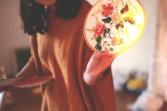 Beautiful woman in the evening sun. The beautiful woman in the evening sun holds her hand-painted plate with Chinese chrysanthemums,In the studio royalty free stock image