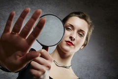 Beautiful woman examining her engagement ring through magnifying glass Royalty Free Stock Image