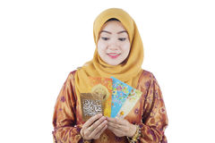 Beautiful woman excited receiving money in envelope during ramadhan festival. Hari raya festival after ramadhan royalty free stock image