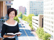 Beautiful woman, executive, teacher, student, rental agent reading a book on a balcony of an apartment Stock Photography