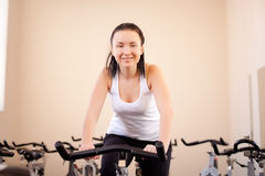 Beautiful woman on an exercise bike Stock Images