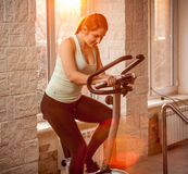 Beautiful woman on exercise bike at gym Stock Photos
