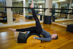 Beautiful woman exercising on arc barrel. In gym Royalty Free Stock Photos