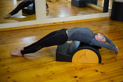 Beautiful woman exercising on arc barrel. In gym Stock Photo