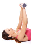 Beautiful woman exercising with barbells. Smiling beautiful young woman exercising with barbells lying on her back extending her arms straight up into the air Royalty Free Stock Images
