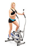 Beautiful woman exercising on a machine. A beautiful woman exercising on a cross trainer machine  on white background Royalty Free Stock Photo
