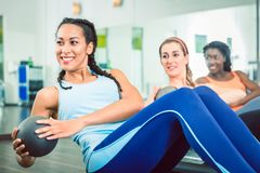 Beautiful woman exercising Russian twist with med ball for strong abs. Beautiful young women exercising Russian twist with med ball from sitting position for royalty free stock images