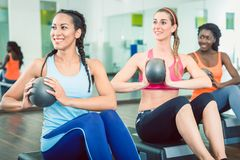 Beautiful woman exercising Russian twist with med ball for strong abs. Beautiful young women exercising Russian twist with med ball from sitting position for stock photo