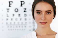 Beautiful Woman With Eye Test Chart At Ophthalmology Office Royalty Free Stock Photos